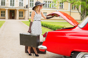 Retro style woman putting suitcase in vintage car