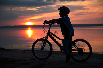 Silhouette of a young boy, at sunset, riding bicycle