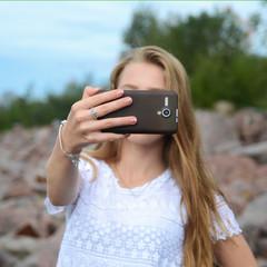 Beautiful blonde girl making selfie with Smartphone, modern teenage lifestyle.