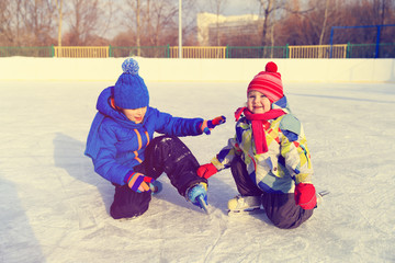 little boy and girl skating together, kids winter sport