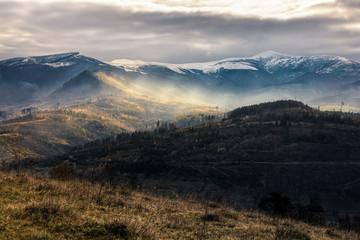 snowy peaks over hillsides in fog