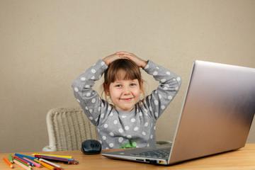 Девочка за компьютером подняла руки