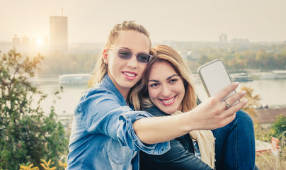 Two beautiful friends making selfie