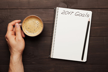 Male hand hold cup of coffee and notebook with goals for 2017. Planning and motivation for the new year concept. Top view.