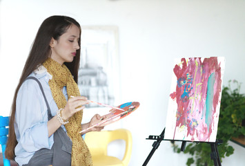 Young female painter painting in her studio. Selective focus and small depth of field.