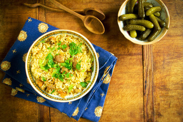 Traditional pilaf and pickled cucumber on a wooden table
