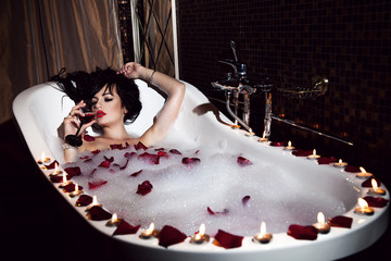 Sexy girl lying in the bath with candles and drink wine, rose pe