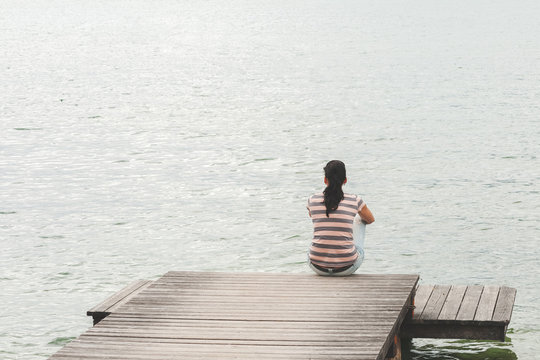Young woman sitting on wooden pier. Girl watching the lake surfa