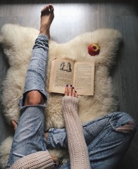 woman on the fur carpet with old book, top view