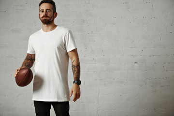 Serious attractive young man in a blank white cotton t-shirt and black jeans holding a vintage rugby ball isolated on white