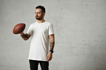 Athletic tattooed hipster wearing a white unlabeled cotton t-shirt, black jeans and large black watch in a studio with a brown old rugby ball