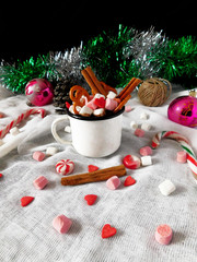 New Year composition made of hot chocolate, Christmas tree decorations and candy canes