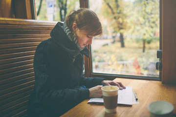 Cup of coffee on the foreground with elegant young woman at the coffee shop wooden table, work break of business people, flare sun light . Cold autumn, the female draws or writes in diary