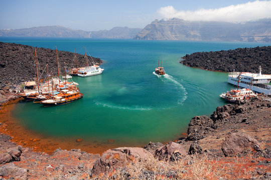 Nea Kameni volcanic island in Santorini, Greece. Ships from Fira