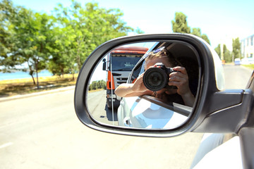 Girl taking photo with camera in moving car