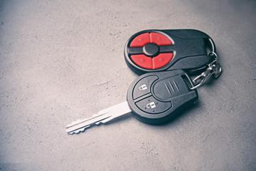 Car key on grey textured background