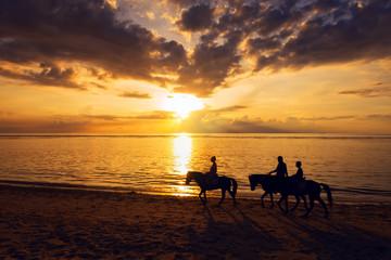 Three rides walking on beach at sunset