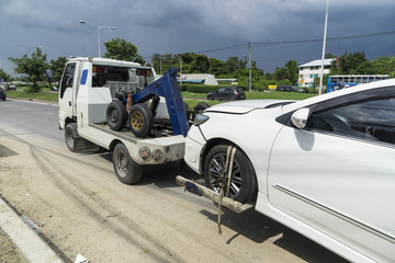 accident car and forklift take a car on the road