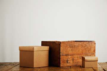 Different sized blank beige corrugated cardboard boxes with covers next to a vintage wine crate isolated on white