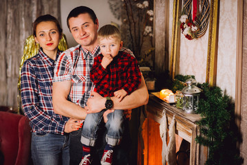 Young family is photographed for Christmas card. Mother, father and little daughter with smile look in camera. They recline on a big bed with bright pillows. Room is decorated with Christmas garlands.