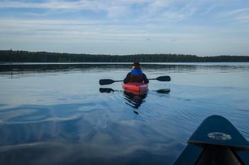 Young man in red kayak on lake