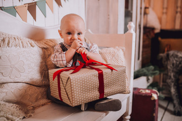 Little boy infant with a gift boxes on christmas or new year holidays.