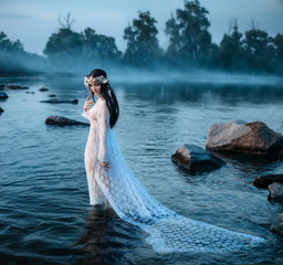 Luxurious lady in sexy, white dress walks into the water