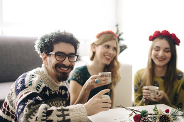 Portrait of smiling man relaxing with friends at Christmas time