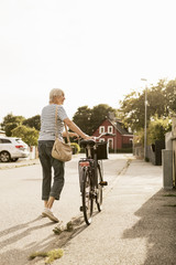 Woman walking with bicycle on road against clear sky