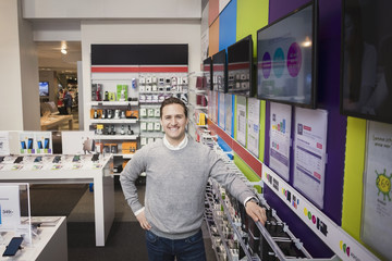 Portrait of cheerful salesman standing in electronics store