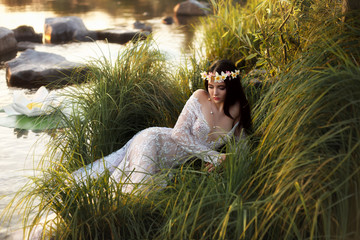 Luxurious, sexy lady, in elegant long dress lying on grass