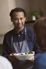 Smiling mature man holding salad bowl while looking at female friend