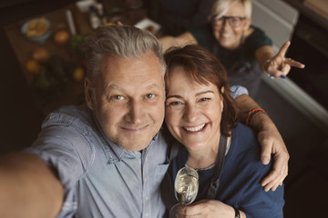 Cheerful mature man with arm around woman while taking selfie in kitchen