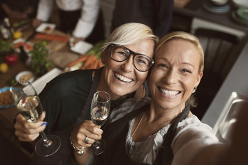 Cheerful mature women holding champagne flutes while taking selfie in kitchen