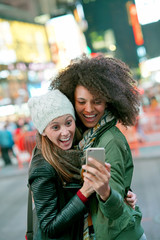 Cheerful girls taking selfie picture at Times Square