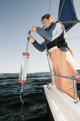Woman collecting water in sampling equipment while standing in a boat