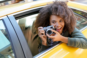 Cheerful girl taking pictures from a yellow cab, New York City