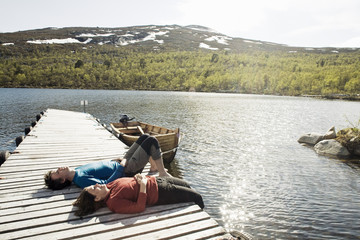 Couple relaxing on pier