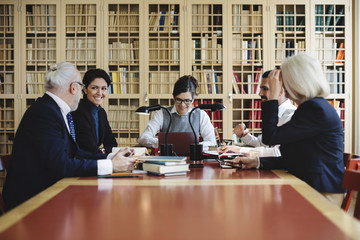 Happy male and female lawyers sitting in board room against bookshelf