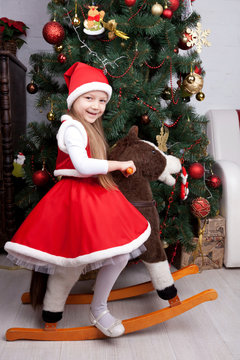 Little girl in Christmas dress playing with toy horse.