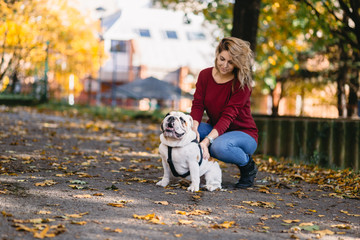 Pretty woman enjoying in park with her adorable English bulldog. Autumn time.