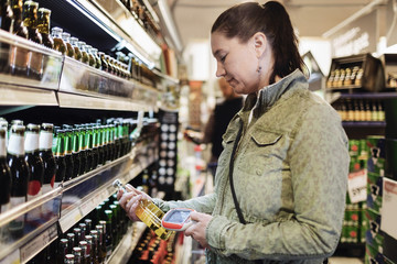 Side view of woman scanning beer bottle in supermarket