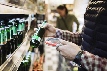 Midsection of male customer scanning beer bottle in supermarket