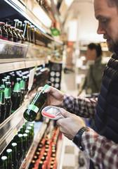 Man using bar code reader on beer bottle in supermarket