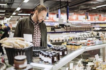 Thoughtful male customer shopping at supermarket