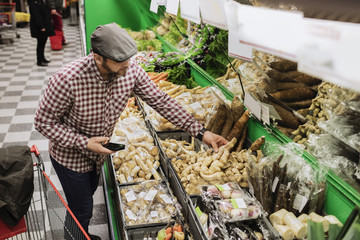 High angle view of man buying root vegetable while holding smart phone in supermarket