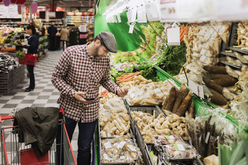 Man holding smart phone while buying root vegetable in supermarket
