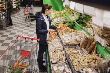High angle view of woman holding phone while buying groceries in supermarket