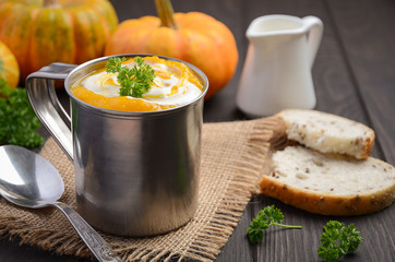 Pumpkin soup with cream and parsley in a mug on wooden background, selective focus