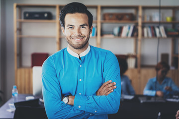 Portrait of successful confident hispanic businessman smiling at the camera in modern office.Horizontal,blurred background .